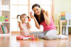 Happy mother and her child playing with colorful logical sorter toy. Cheerful mother and her child girl playing with colorful logical sorter toy Stock Photography