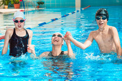 Happy mother with her children jumping out of the water royalty free stock photo