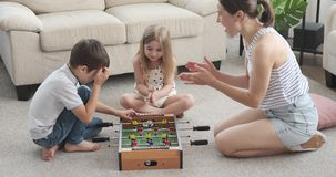 Happy family playing foosball at home. Happy mother with her children playing foosball game at home stock video footage