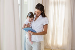 Happy mother with her cute baby girl using tablet Stock Photos