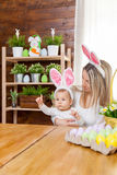 Happy mother and her cute child wearing bunny ears, getting ready for Easter Stock Photo