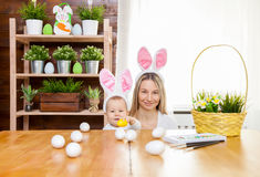 Happy mother and her cute child wearing bunny ears, getting ready for Easter Royalty Free Stock Image