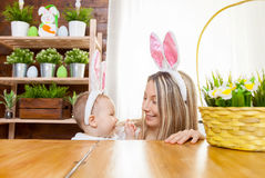 Happy mother and her cute child wearing bunny ears, getting ready for Easter Stock Images