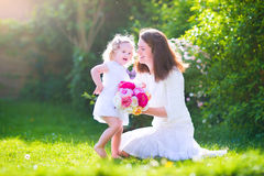 Happy mother and her cute daughter in the garden Stock Photos
