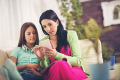 Happy mother and her cute teen daughter are looking at mobile phone. While sitting on sofa at home Stock Photography