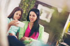 Happy mother and her cute teen daughter are looking at mobile phone Royalty Free Stock Photography