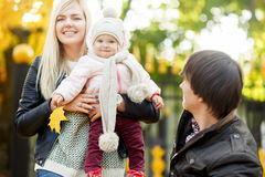 Happy mother with her daughter and dad in autumn park Royalty Free Stock Images