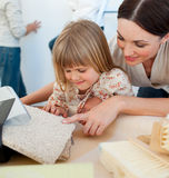 Happy mother and her daughter decorating a room Stock Photos