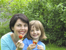 Happy mother and her daughter eating strawberries Stock Photos