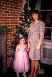 Happy mother with her daughter by the fireplace near Christmas tree Stock Photo