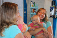 Happy mother with her daughter in front of mirror Royalty Free Stock Photos
