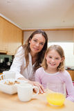 A happy mother and her daughter having breakfast. Portrait of a happy mother and her daughter having breakfast in a kitchen Royalty Free Stock Photo