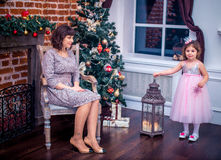Happy mother with her daughter playing near the Christmas tree Royalty Free Stock Photos