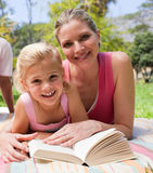 Happy mother and her daughter reading in a park Royalty Free Stock Photography