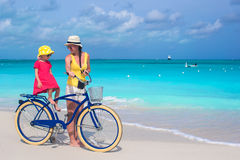 Happy mother and her daughter riding bicycles on a tropical beach Stock Image