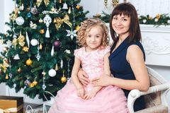Happy mother with her daughter sit near a white fireplace next to a tree decorated with toys. Happy mother with her daughter sit near a white fireplace next to a Stock Photography