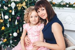 Happy mother with her daughter sitting near a Christmas tree looking into the camera and smiling. Happy mother with her daughter sit near a white fireplace next Stock Image
