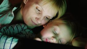 Happy mother with her daughter. Together I play on the tablet, lie side by side face to face in bed stock video