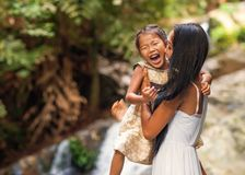 Happy mother with her daughter in the tropics near the waterfall. Mothers day Royalty Free Stock Images