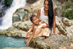 Happy mother with her daughter in the tropics near the waterfall. Mothers day Royalty Free Stock Photos