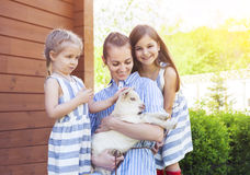 Happy mother and her daughters with baby goats Royalty Free Stock Image