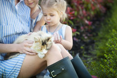Happy mother with her daughters holding cat against nature Royalty Free Stock Images