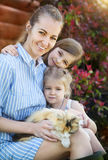 Happy mother with her daughters holding cat against nature Royalty Free Stock Photos