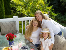 Happy mother and her daughters sharing a hug during breakfast Stock Photos