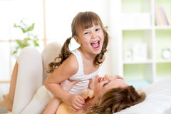 Happy mother and her kid tickle, play and laugh in Stock Photo