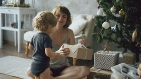 Happy mother and her little daughter unpack gift box near the Christmas tree at home. Happy mother and her little beautiful unpack gift box near the Christmas stock video footage