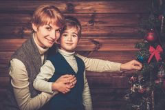 Happy mother and her lIttle boy decorating tree Royalty Free Stock Photos