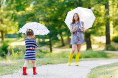 Happy mother and her little cute kid girl in rain boots. Playing together in summer sunny park, on warm day Royalty Free Stock Images
