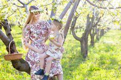 Happy mother and her little daughter in a blossoming garden Royalty Free Stock Photos