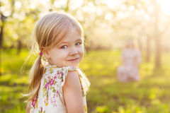 Happy mother and her little daughter in a blossoming garden Stock Photography
