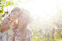 Happy mother and her little daughter in a blossoming garden Stock Photos