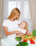 Happy mother and her little daughter in the kitchen Stock Photos
