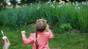 Happy Mother and her little Daughter playing together outdoor, blowing soap bubbles, having fun on backyard. Nature stock video