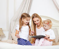 Happy mother and her little daughters having fun using a tablet Royalty Free Stock Photos