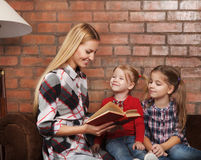 Happy mother and her little daughters indoors. Brick background Royalty Free Stock Images