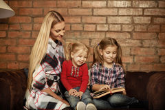 Happy mother and her little daughters indoors Stock Photos