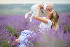 Happy mother and her little son phaving fun in a lavender field. Happy young mother and her little son posing in purple field of lavender flowers Stock Photo