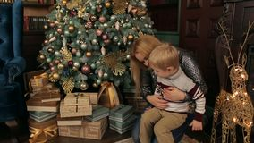Happy mother with her son near the Christmas tree. Happy mother and her little son are playing and having fun near the Christmas tree on the eve of the new year stock footage