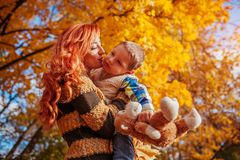 Happy mother and her little son walking and having fun in autumn forest. Royalty Free Stock Images