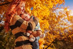 Happy mother and her little son walking and having fun in autumn forest. Royalty Free Stock Photo
