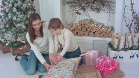 Happy mother and her little son wrapping up Christmas gifts at home stock video