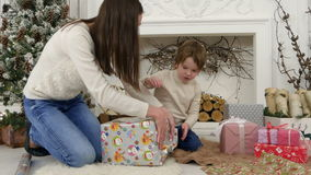 Happy mother and her little son wrapping up Christmas gifts at home stock video footage