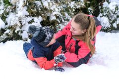 Happy mother with her son in an arms embrace on the snow. Happy mother with her son embracing outdoors on the snow Royalty Free Stock Photos