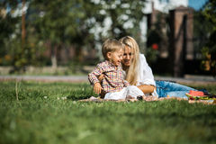 Happy Mother with her son in the garden. Mother with kids have fun on the grass royalty free stock images