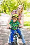 Happy mother with her son having fun, riding a bicycle.  Royalty Free Stock Photography