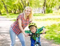 Happy mother with her son having fun, riding a bicycle Royalty Free Stock Photography